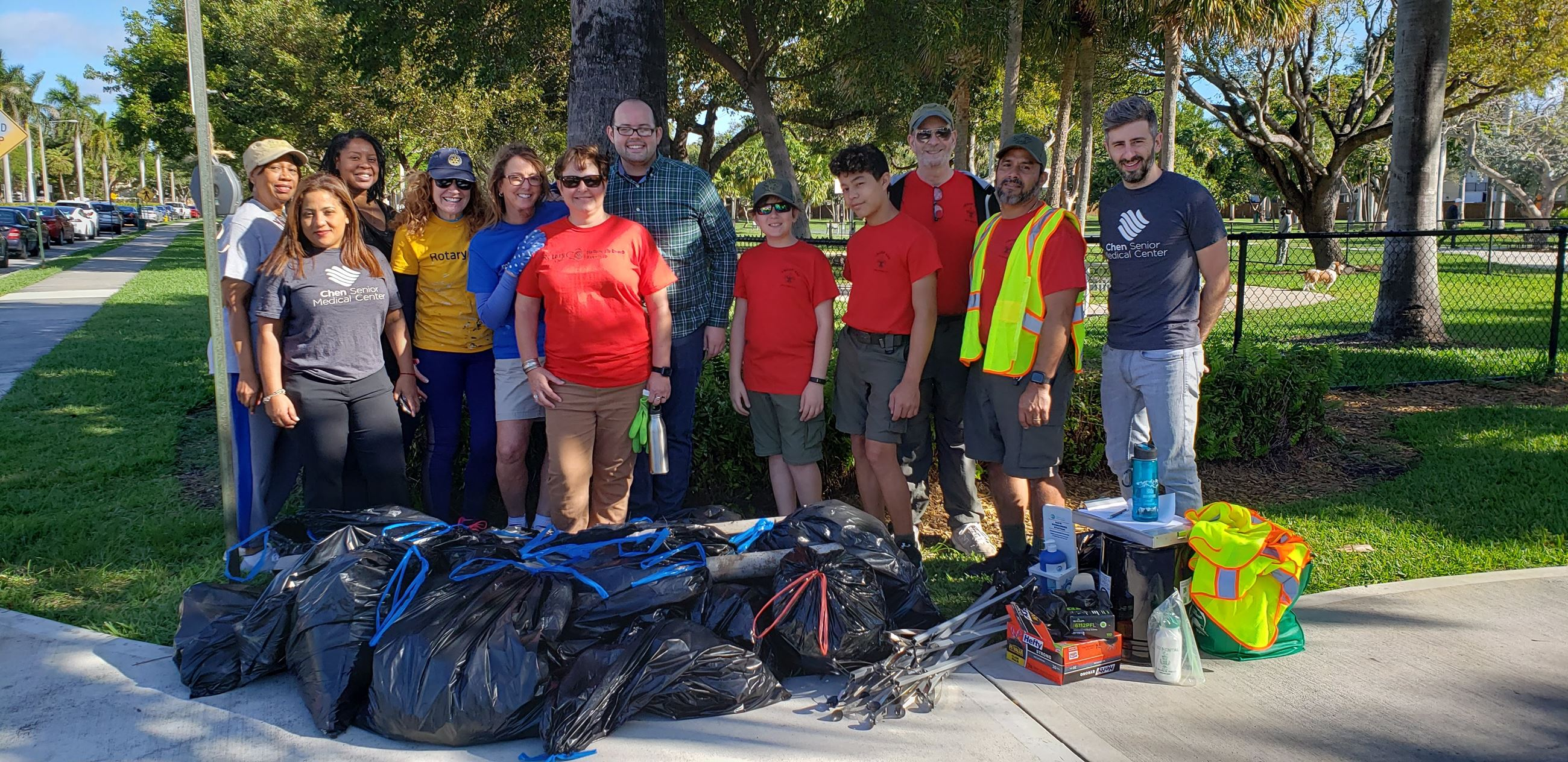 group of volunteers posing behind trash bags full of litter they picked up